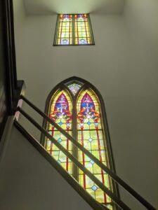 Stairs leading to the mezzanine and the original stained glass windows